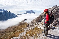 Climber on the way up to Gran Cir mountain above the Gardena Pass, Dolomites, Val Gardena valley and Langkofel mountain at the back, province of Bolza...