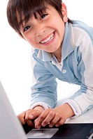 Portrait of cute caucasian boy smiling with laptop over white background