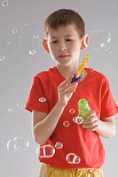 boy in a red T_shirt blows soap bubbles, on grey background