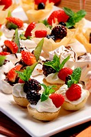 Brightly coloured finger fruit desserts on a white platter