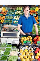 A greengrocer standing behind the display counter surrounded by fresh fruit and vegetables