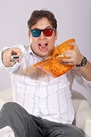 A young man watching a movie in 3D, with stylish 3D glasses and eating popcorn.