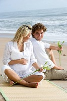Happy young pregnant couple relaxing on beach sitting together on sand