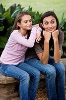 Teenage girl with younger sister sitting together on bench outdoors