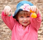 A happy little girl in pink with a hat opens an orange Easter Egg to get the candy inside during egg hunt.