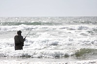 A man surf fishing in the waves.