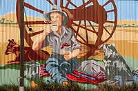 Hand_painted wall mural on corrugated iron of an Australian farmer drinking a hot beverage with his two dogs, Carnamah, Western Australia, Australia