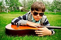 Kid in sunglasses playing a guitar outdoors