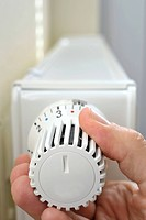 Hand adjusting the temperature on a thermostatic valve of a radiator