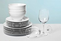 Dishes and wine glasses on pale blue background