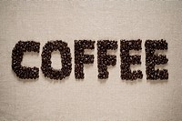 Coffee spelled with Coffee beans on a sack background.