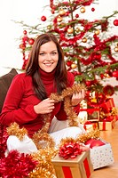 Attractive young woman with Christmas decoration in front of tree