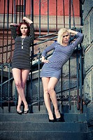 two girls posing in short striped dresses