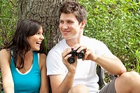 Attractive young woman laughs as her male companion holds a pair of binoculars.