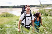 Young backpacking couple hike up a grassy hill.