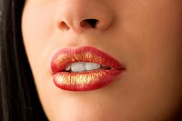 closeup of woman mouth with red and golden colored lips