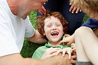 Young boy laughs as his family tickles him.