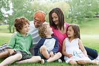 Portrait of a family of five sitting on a park lawn and smiling at one another.