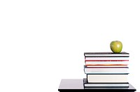 Horizontal image of a stack of books with a green apple on white