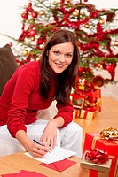 Attractive brunette writing Christmas cards in front of tree