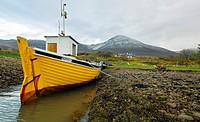 Small fishing boat 'Murrisk' moored at low tide, with a snow dusted Croagh Patrick in the background, Murrisk, Westport, County Mayo, Republic of Irel...