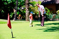 Father and son playing golf. Focus on flag.