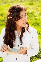 Young brunette woman in white with book looking sideways