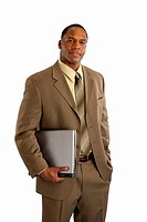 Serious African American businessman holding laptop computer on white background