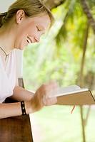 Blonde Frau liest lachend an einer Balkonbrüstung ein Buch Model: Lara