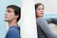 Junges Paar sitzt auf den gegenüberliegenden Seiten einer Steinwand Model rechts: Marlene