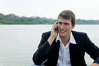 Junger Manager sitzt in einem Boot im See und telefoniert lachend mit seinem Handy