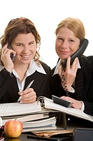 Zwei weibliche Büroangestellte telefonieren zusammen und bearbeiten Akten