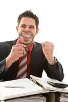 Junger Geschäftsmann an seinem Arbeitsplatz hält sich beim Jubeln und Grinsen eine Lupe vor den Mund Model: Kosta Lales