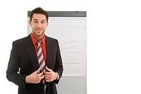 Junger Geschäftsmann vor einem Flipchart schaut lächelnd und stolz nach ein Referat Model: Kosta Lales