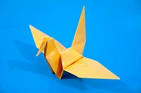 Origami yellow bird with blue background