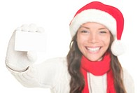 Christmas woman showing business card / blank white sign with copy space. Young woman smiling in Santa hat, sweater and gloves. Isolated on white back...