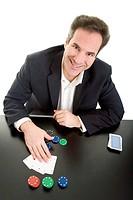 Lachender Mann mit Pokerchips legt vier Asse auf den Tisch