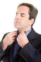 Geschäftsmann mit Handy in der Hand zupft gelassen am Kragen