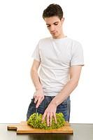 Junger Mann schneidet einen Lollo Bionda_Salat Lactuca sativa var. crispa auf einem Küchenbrett