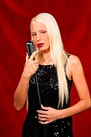Young blond girl sings in the evening dress with microphone
