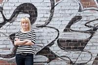 Junge Frau lehnt selbstsicher mit verschränkten Armen an einer Mauer mit Graffito