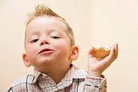 Vierjähriger Junge kaut lachend ein Brötchen