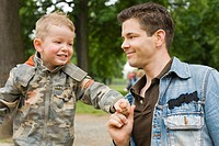 Vater hält lächelnd seinen vierjährigen Sohn an der Hand fest