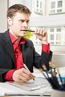 Mann sitzt am Schreibtisch und zeichnet auf einem Grafiktabklett während er auf einen Bleistift beißt