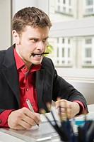 Mann am Schreibtisch zeichnet mit einem Grafiktablett und beißt dabei frustriert auf einen Bleistift