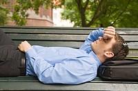 Mann in Businesskleidung liegt auf einer Parkbank und macht ein Nickerchen