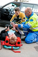 Multi_disciplinary medical team with a fireman and a paramedic, kneeling around a stretcher, and strapping an injured woman down