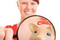 Lachende junge Frau hält eine Lupe vor ihr Sparschwein