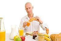 Mann im weißen Hemd sitzt am Frühstückstisch und steckt die Spitze eines Croissants in ein Marmeladenglas