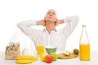Mann im weißen Hemd sitzt am Frühstückstisch und lehnt sich zurück